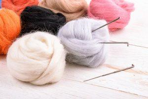Needle felt – wool and needles close up