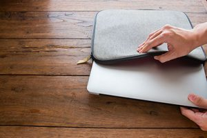 hand pulling laptop out of laptop bag