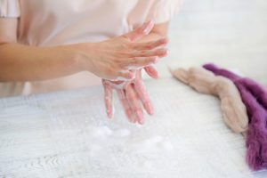 Photo of a woman with wet soapy hands, ready to start the process