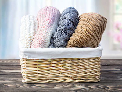 Knitted woolen clothes rolled in a basket