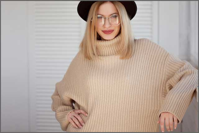 Felt hat and beige sweater worn by a beautiful woman
